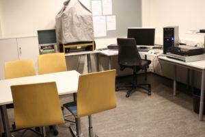 Ryhmätila Lukossa on kaksi pöytää. Toisen pöydän ympärillä on neljä tuolia. Toisella pöydällä on digitointiin tarkoitettuja laitteita, kuten tietokone, levysoitin ja VHS-videonauhuri. Pöydällä on myös mikrokortinlukulaite ja mikrofilminlukulaite.