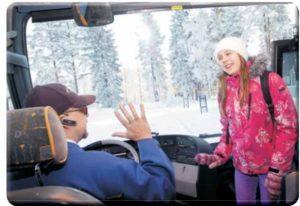 Talvinen kuva, jossa oppilas astuu koulubussiin ja bussikuski tervehtii oppilasta kättä heiluttaen.