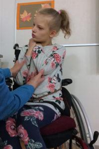 Kuva tyttö pyörätuolissa