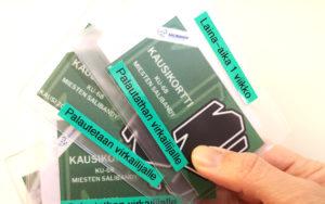 Käsi, joka pitelee kolmea urheiluseurojen kausikorttia