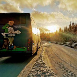 Kirjastoauto Kotikujan Konsta talvisessa maisemassa auringon noustessa.