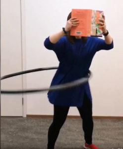 Nainen pyörittää hulavannetta ja pitää kasvojensa edessä kirjaa