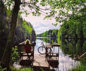 Kuvassa nainen, pyörä ja järvi.