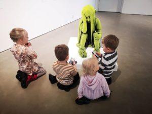 Lapsia istuu lattialla Sammaltyttö-teoksen edessä.