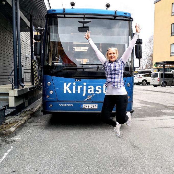 Kirjastoauton edessä tyttö hyppää ilmaan.