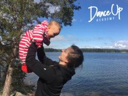Sivuprofiilissa oleva nainen pitelee ojennetuilla käsivarsillaan punavalkoraitaiseen haalariin puettua vauvaa. Taustalla kesäinen järvimaisema.