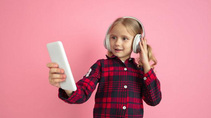 Vaaleanpunaisella taustalla punaruutuiseen paitaan pukeutunut tyttö, jolla on kädessään puhelin ja korvilla kuulokkeet