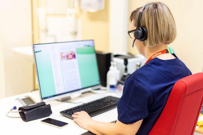 Sairaanhoitaja istuu työpöydän äärellä ja käyttää tietokonetta kuulokkeet päässään.