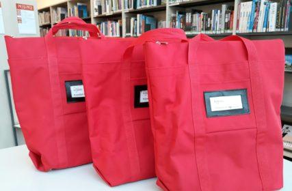 Kolme punaista markiisikassia,taustalla kirjahylly